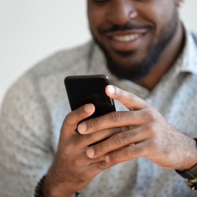 Close up of smiling african American man hold new model modern cellphone texting chatting, happy biracial male use fast connection mobile internet on cellphone browsing web. Technology concept